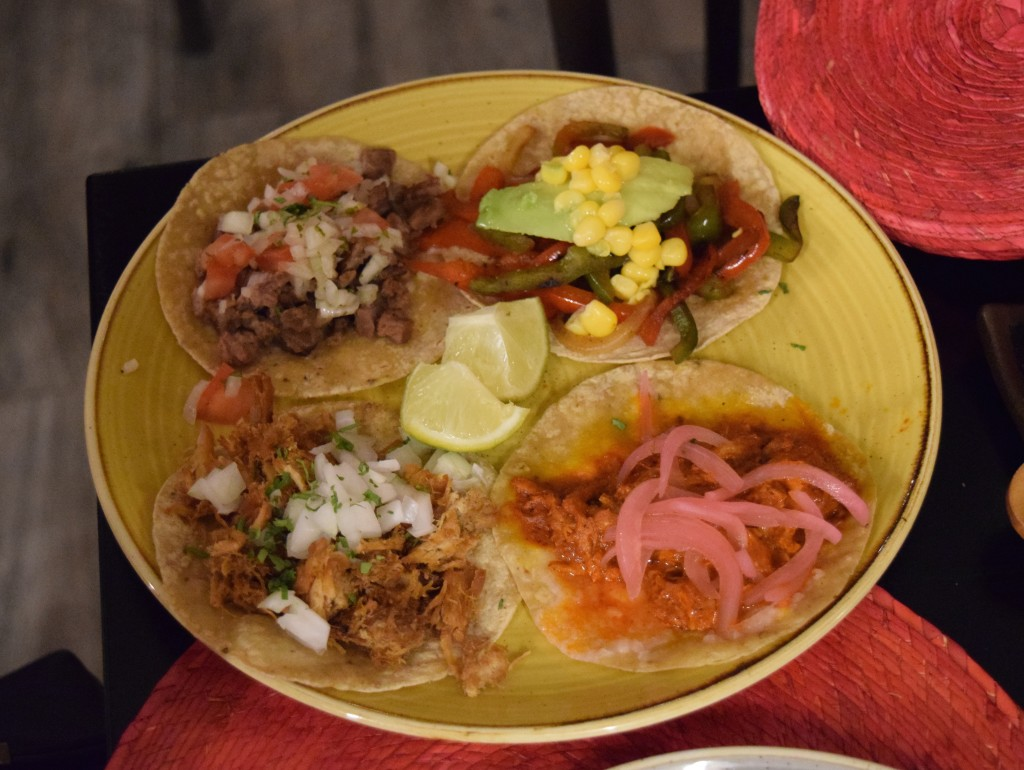 Mexican tacos with pork, beef, vegetables, and pickled onions