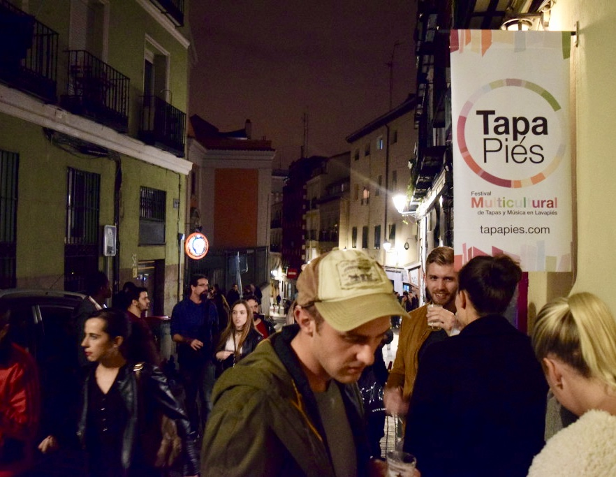 A bar advertises its participation in Tapapiés with the festival's official poster.